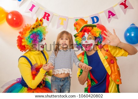 clown girl and clown boy at the birthday of a child. Party for children. Clowns and little girl show different emotions  #1060420802