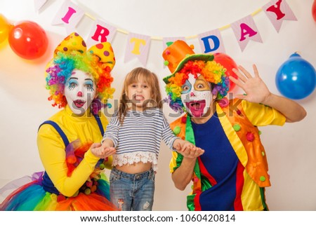 clown girl and clown boy at the birthday of a child. Party for children. Clowns and little girl show different emotions  #1060420814
