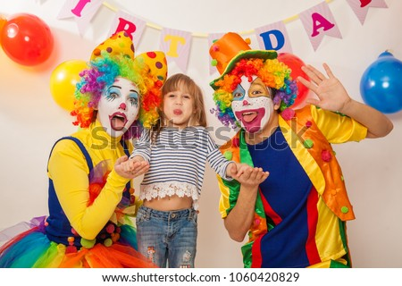 clown girl and clown boy at the birthday of a child. Party for children. Clowns and little girl show different emotions  #1060420829