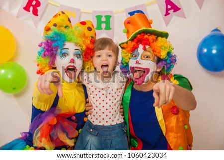 clown boy and clown girl on birthday girl. Party for children. Clowns amuse the child #1060423034