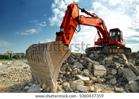 Crawler excavator on demolition site. Front view of a big crawler excavator working on demolition site. #1060437359