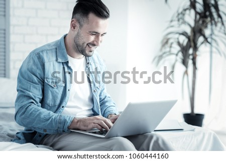 Smart freelancer. Happy positive cheerful man holding a laptop and typing the text while working as a freelancer #1060444160