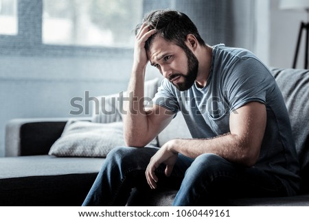 Unpleasant pain. Sad unhappy handsome man sitting on the sofa and holding his forehead while having headache #1060449161