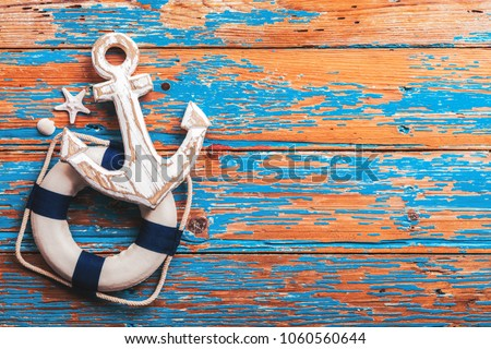 Summer concept, Anchor and lifebuoy on distressed wood table