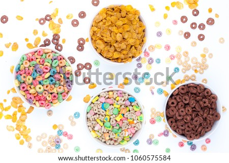 Four bowls of cereals and cereals scattered around the table on white background. A bowl of colored cereals, one of chocolate rings, one with cereals and marshmallow, and one with corn flex. Top view. #1060575584