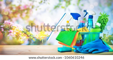 Basket with cleaning items on blurry spring background #1060610246