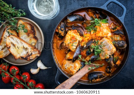 Traditional French Corsican fish stew with mussels and garlic baguette as top view in a pot #1060620911