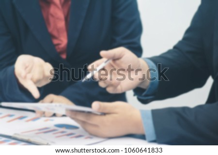 Blurred image of business team meeting present, Manager and secretary working with new startup project with laptop,calculator and smart phone on desk in the office. #1060641833