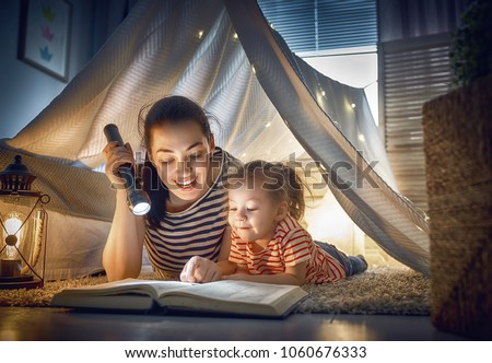 Family bedtime. Mom and child daughter are reading a book in tent. Pretty young mother and lovely girl having fun in children room. #1060676333