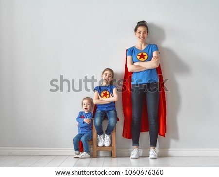 Mother and her children playing together. Girls and mom in Superhero costumes. Mum and kids having fun and smiling. Family holiday and togetherness.