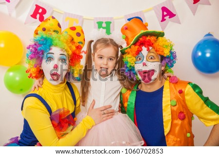 clown boy and clown girl on birthday girl. Party for children. Clowns amuse the child #1060702853