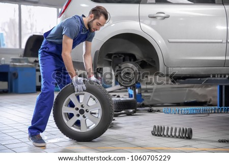 Young mechanic with car tire in service center #1060705229
