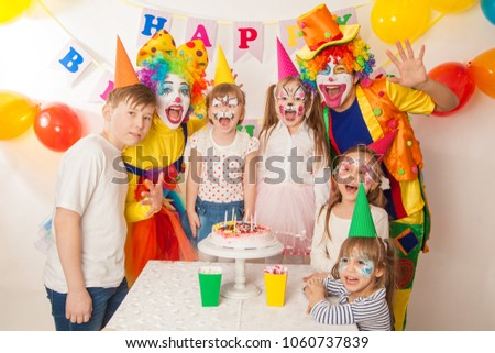clown girl and clown boy at the children birthday party. Festive table with a beautiful cake. Blow out candles and make a wish #1060737839