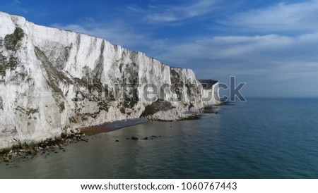 Aerial bird view picture of The White Cliffs of Dover they are cliffs that form part of the English coastline facing the Strait of Dover and France and are part of the North Downs formation #1060767443
