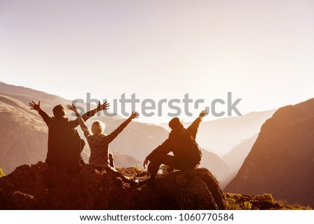 Three happy friends greetings sunset at mountain top with raised arms. Travel and advertures concept with place for text #1060770584