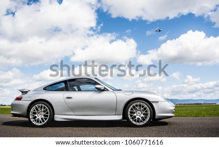 April 2, 2018 Eugene Oregon - A silver Porsche 911 body style 996 sits on an empty road under a sunny cloud filled sky near some green fields of grass. #1060771616