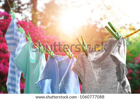 Rope with clean clothes outdoors on laundry day Royalty-Free Stock Photo #1060777088