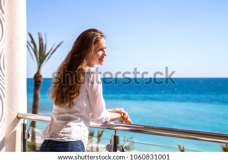The beautiful girl standing on a balcony of apartments looking at the seaside. #1060831001