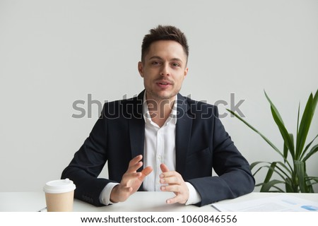 Confident CEO looking at camera talking about company strategy and business plan, explaining corporate success. Young entrepreneur shooting for online webinar, recording video blog. Headshot portrait Royalty-Free Stock Photo #1060846556