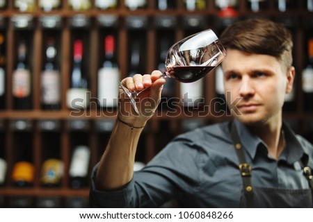 Bokal of red wine on background, male sommelier appreciating drink #1060848266