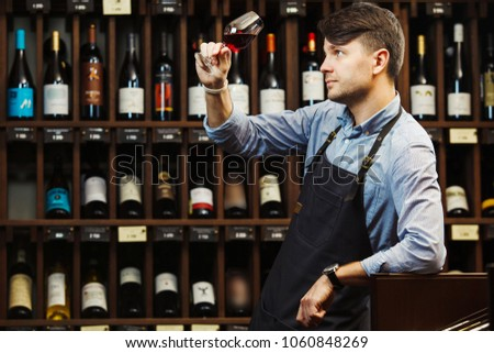 Bokal of red wine on background, male sommelier appreciating drink #1060848269