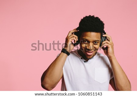 Portrait of a cool guy with headphones smiling and looking at camera, enjoying music, on pink background #1060851143