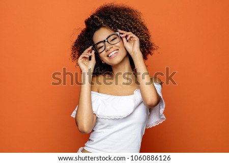 Portrait of beautiful smiling black woman in glasses  Royalty-Free Stock Photo #1060886126