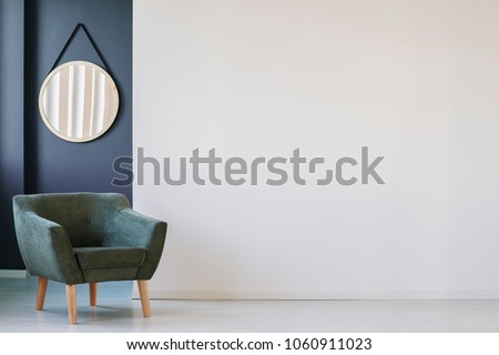 Green armchair against blue wall with round mirror in living room interior with copy space on white wall #1060911023