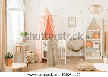 White bookcase with plush toys and decorations in a cute, cozy, white and peach pink scandinavian nursery interior Royalty-Free Stock Photo #1060911122