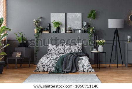 Double bed with floral bedding and dark blankets standing in grey bedroom interior with fresh plants, paintings and lamp #1060911140