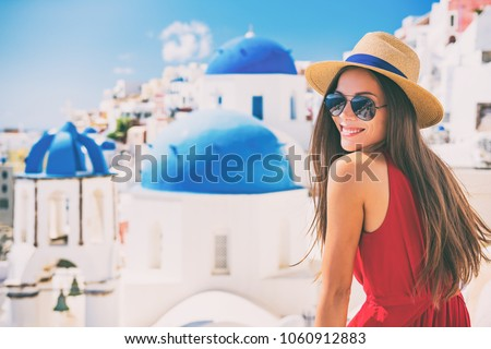 Travel Europe summer holiday girl enjoying Oia, Santorini Greece cruise vacation. Sun getaway Asian woman smiling in hat and sunglasses. #1060912883
