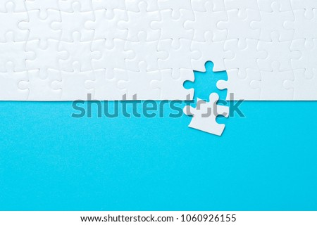 Blue background made from white puzzle pieces and place for your content #1060926155