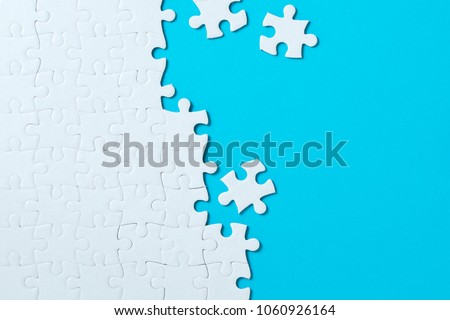 Unfinished white jigsaw puzzle pieces on blue background Royalty-Free Stock Photo #1060926164