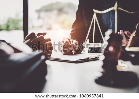 Business woman and lawyers discussing contract papers with brass scale on wooden desk in office. Law, legal services, advice, Justice concept. #1060957841