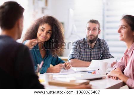meeting at the startup office. A young man leads a multi-ethnic working group.Focus on a black woman #1060965407
