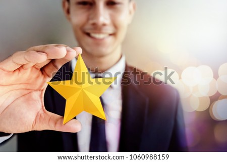 Success in Business or Personal Talent Concept. Happy Businessman in black suit Smiling and Showing a Golden Star in Hand Royalty-Free Stock Photo #1060988159