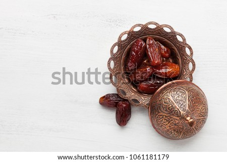 Plate of pitted dates on a white wooden background. Top view Royalty-Free Stock Photo #1061181179