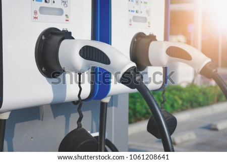 electric vehicle charging (Ev) station with plug of power cable supply for Ev car. Smart enegy.Flare light effect #1061208641