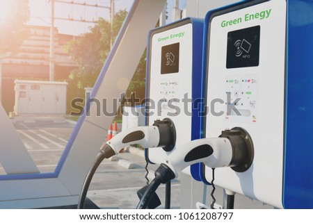 electric vehicle charging (Ev) station with plug of power cable supply for Ev car. Nfc payment. Smart enegy. Flare light effect. #1061208797