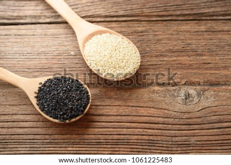 Black sesame seed on wooden table. #1061225483