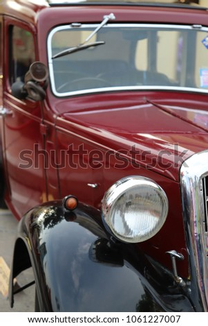 Closeup of a classic red  and black vintage car. Showing an ancient vehicle before 1960. Vertical view. #1061227007