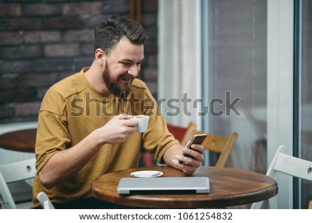 Young man sitting in cafe and using smart phone. #1061254832