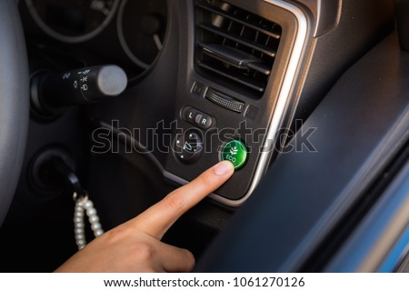 Woman Hand is Pressing Eco Mode Botton in Vehicle Car, Close-Up of  Female Hand is Pushing Ecology Saving Energy Function for Personal Transport. Power Save Engine and Pollution Environment Concept #1061270126