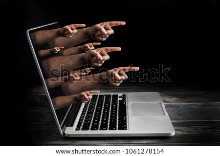 Cyber bulling concept with fingers from the screen blame user #1061278154