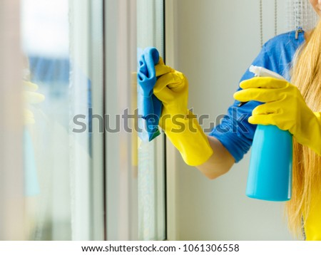 Female hand in yellow gloves cleaning window with blue rag and spray detergent. Spring cleanup, housework concept #1061306558