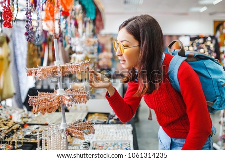 Trendy hipster asian woman looking for fancy jewelry and accessories in a flea market shop