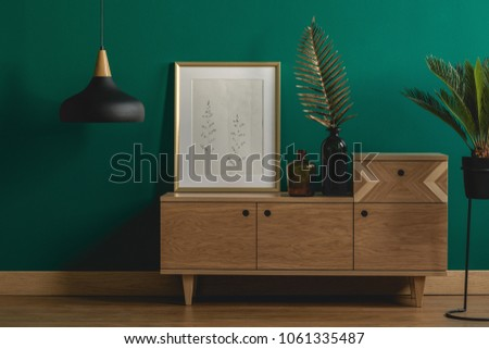 Industrial pendant light next to a stylish dresser and an art poster in a golden frame by a dark green wall of a modern bedroom interior #1061335487