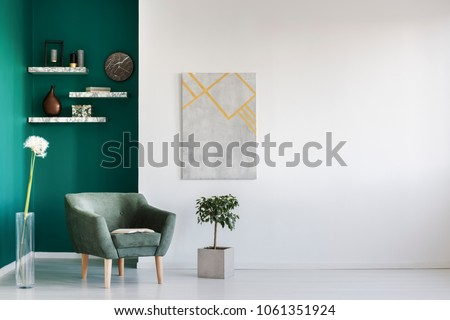 Green armchair between dandelion and plant in living room interior with copy space and grey painting Royalty-Free Stock Photo #1061351924