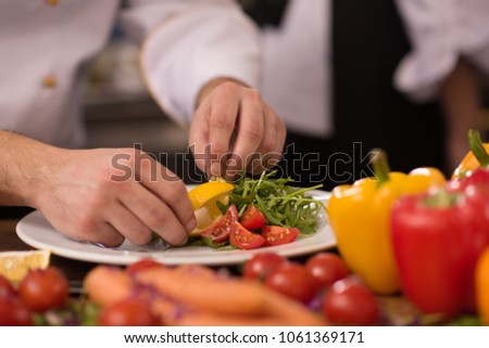 chef serving vegetable salad on plate in restaurant kitchen #1061369171