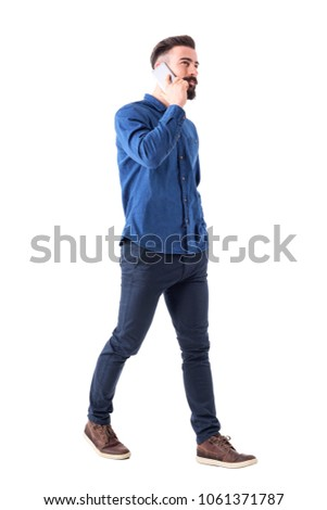 Successful stylish young male ceo walking and talking on the cell phone looking up. Full body isolated on white background. #1061371787